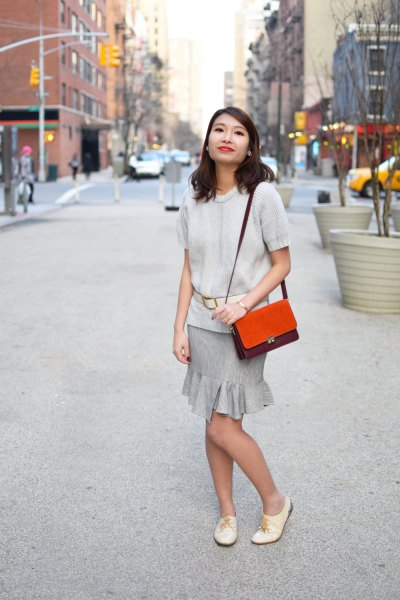 Ivory short-sleeved sweater with a gray frilled mini skirt and white oxford leather shoes