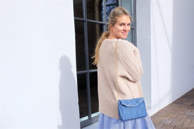 Ivory cardigan with a light blue, flared midi skirt and shoulder bag made of denim