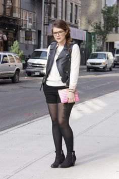 Leather vest with a white sweater and a black mini skirt