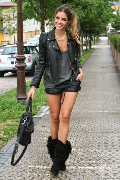 Leather jacket with a gray tank top and fringed boots in the middle of the calf