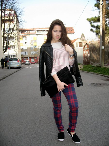 Leather jacket with dark blue and red checked pants and a black clutch