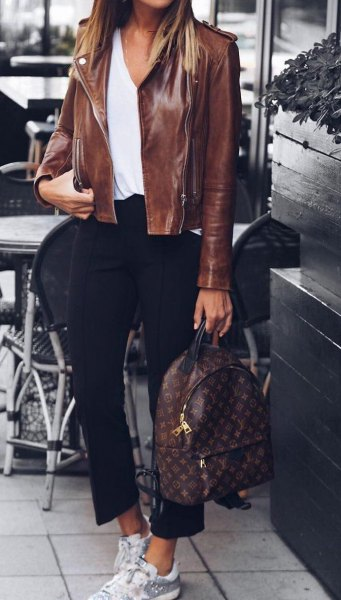 Leather jacket with a white blouse with a scoop neckline and short black pants