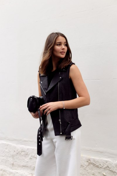 Leather vest, white pants with wide legs