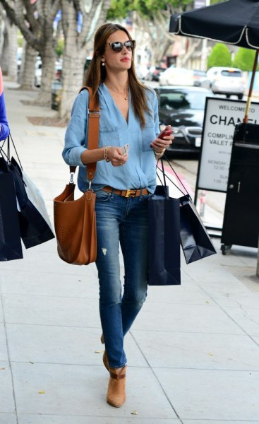 Light blue shirt with buttons, jeans with a belt and light brown boots