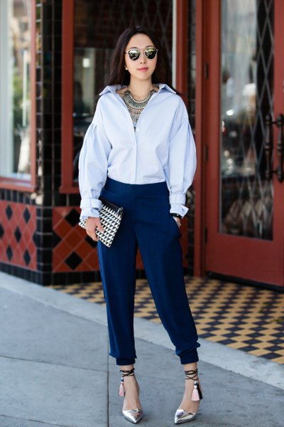 Light blue shirt with buttons and dark tapered, pleated jeans