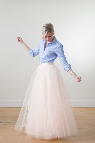 Light blue shirt with buttons and white, floor-length, flowing skirt with a high waist