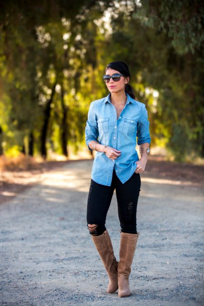 Light blue chambray shirt with buttons, black jeans and flat knee high boots made of gray suede