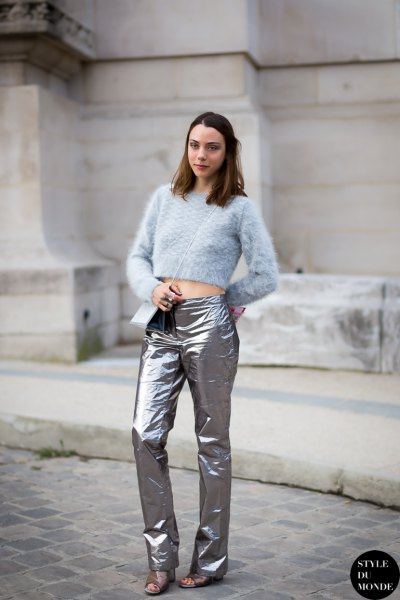 Light blue, cropped knitted sweater with silver trousers and sandals