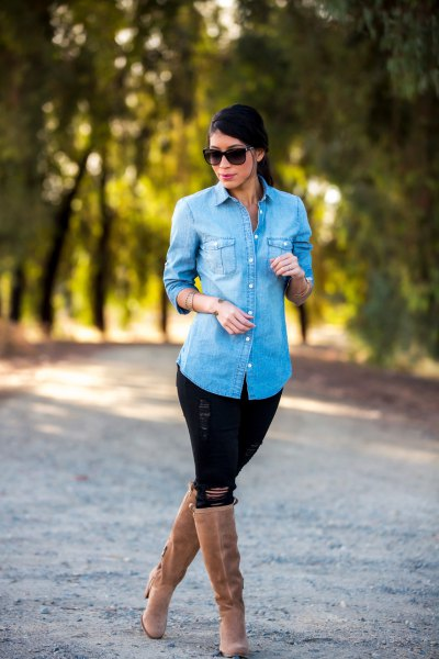 Light blue denim shirt with black jeans and knee-high boots with camel heels