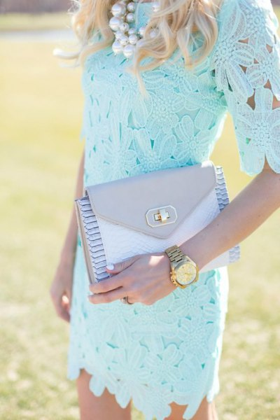 Light blue, figure-hugging lace dress with half sleeves and a matching clutch