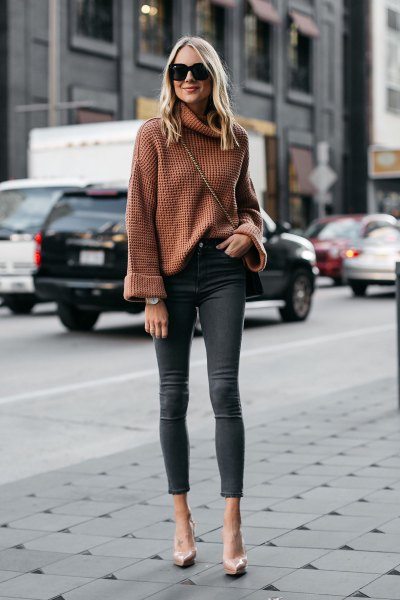Light brown wide-sleeved sweater with a waterfall neckline and gray skinny jeans