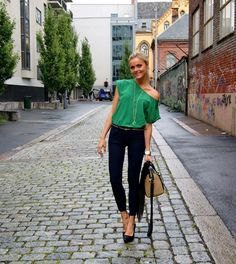 Light emerald green top with one shoulder and black skinny jeans