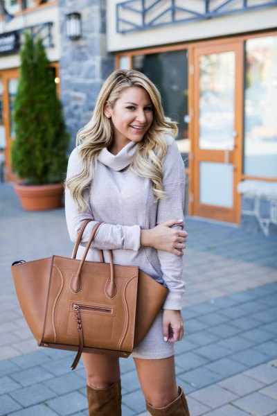 Light gray sweater dress with a waterfall neckline and brown over-the-knee boots
