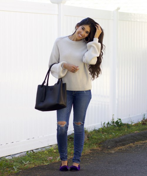 Light gray sweater with a round neckline, ripped jeans and dark blue velvet flats