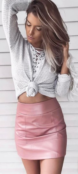 Light gray knitted sweater with a pink figure-hugging mini skirt made of leather