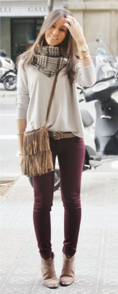 light gray sweater with skinny jeans and shoulder bag with fringes