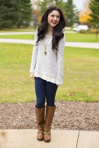 Lightly mottled tunic sweater with dark blue leggings and brown leather boots