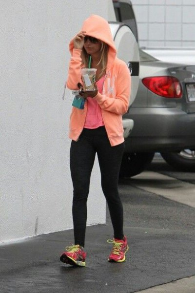 Light yellow hoodie with black training leggings and gray sneakers