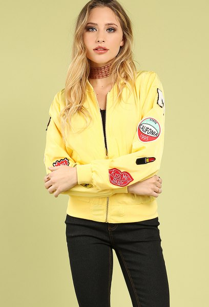 Light yellow patch bomber jacket with black skinny jeans