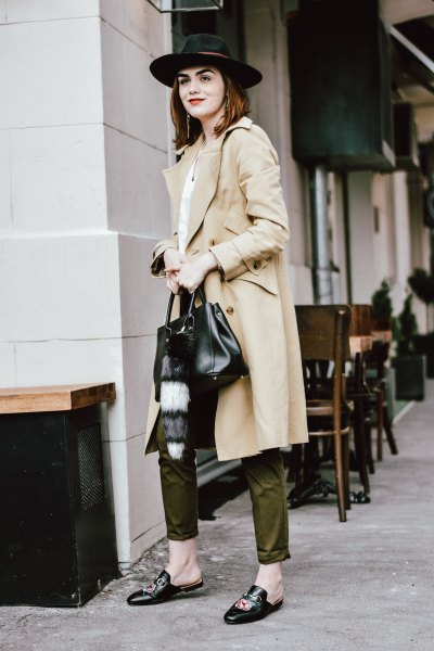 long beige trench coat with green trousers and felt hat