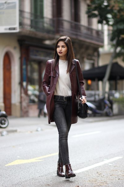long chestnut brown leather jacket with white sweater and gray jeans