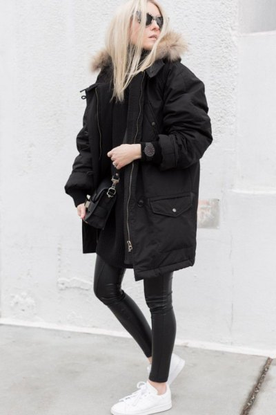 long oversized black winter coat with dark gray skinny jeans and white sneakers