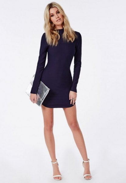 Long-sleeved, figure-hugging mini dress in navy blue with a silver metallic clutch