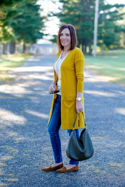 Mustard yellow longline cardigan with white vest top and blue jeans