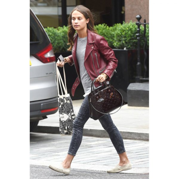 Maroon leather jacket with a gray T-shirt and skinny jeans with cuffs