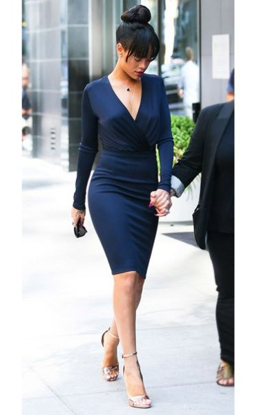 Midnight blue, figure-hugging midi dress with a deep V-neckline and silver heels