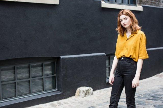 Mustard-colored shirt with wide sleeves and black high-rise jeans