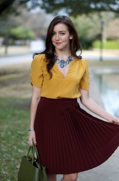 Mustard shirt with a silver statement chain with a burgundy pleated skirt