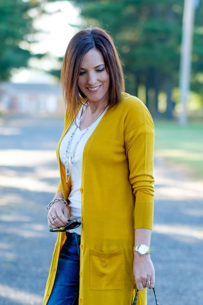 Mustard yellow knitted sweater with a white t-shirt with a scoop neck and blue jeans