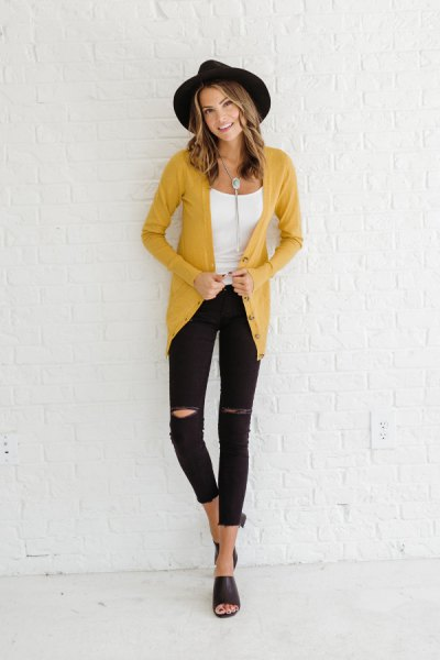 mustard-yellow cardigan with a black felt hat and ripped jeans