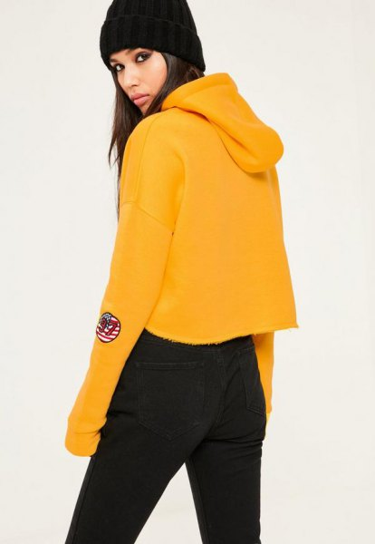 Mustard yellow cropped hoodie with black high-waisted jeans