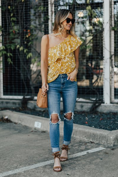 Mustard yellow top with a shoulder ruffle and ripped jeans