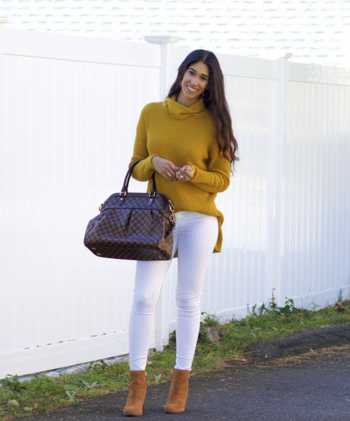 Mustard-yellow, ribbed sweater with a cowl neckline and white skinny jeans