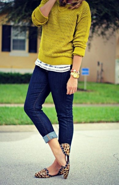 Mustard yellow sweater with dark blue skinny jeans with cuffs and flat shoes with animal print