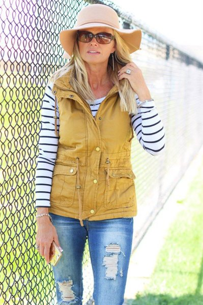 Mustard-yellow utility vest with black and white striped long-sleeved T-shirt