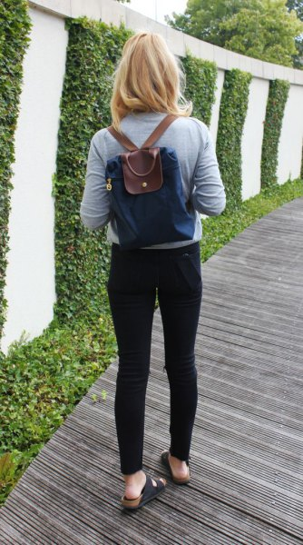 dark blue and brown backpack wallet with gray long-sleeved T-shirt