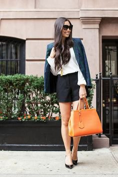 Navy blazer with black, flowing shorts and leather handbag