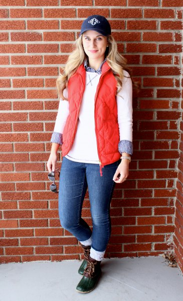 Navy blue baseball cap with white sweater and quilted vest