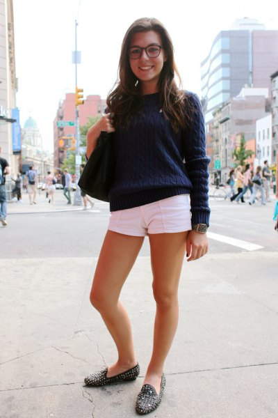 Dark blue cable knit sweater with white mini shorts and black slippers with spikes