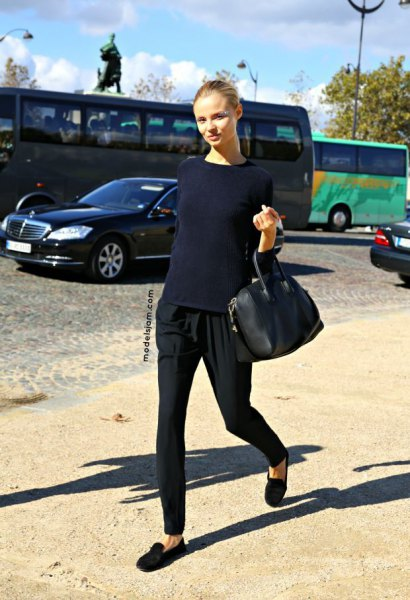Dark blue, fitted sweater with black trousers with conical legs and black suede low shoes