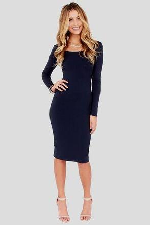 Dark blue long-sleeved midi dress with a boat neckline and white heels with open toes