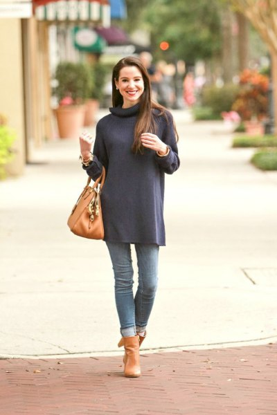 Dark blue long-sleeved turtleneck tunic with cuffed jeans and orange-colored boots