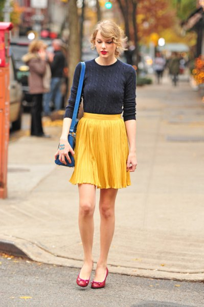Dark blue, figure-hugging sweater with a yellow pleated mini skirt