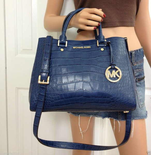Dark blue leather handbag with a green crop top and mini shorts