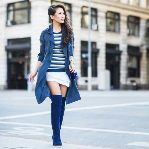 Navy longline trench coat with a white wrap skirt and blue overknee boots