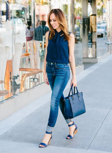Navy sleeveless shirt with buttons and blue high-waisted skinny jeans